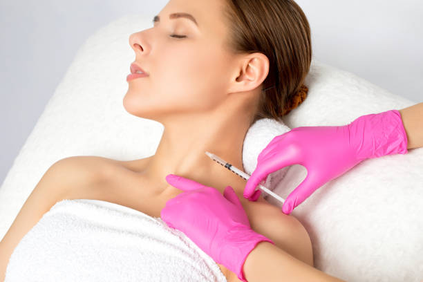 Woman with beautiful clean skin. Cosmetologist does injections on the neck against wrinkles and sagging skin of a beautiful woman. Women's cosmetology in the beauty salon. stock photo