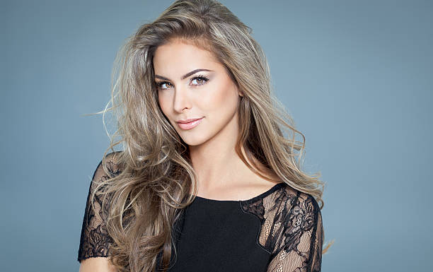 Woman With Beautiful Hair Young beautiful woman with long hair and highlights posing in black silk lace top. Smiling fashionable woman. highlights hair stock pictures, royalty-free photos & images