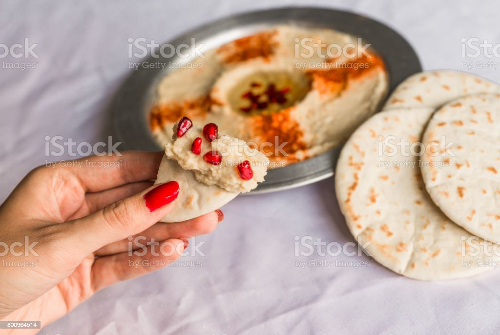 Woman with beautiful hands eating pita bread with hummus and pomegranate seeds. Healthy food, fitness, and sport diet concept. stock photo