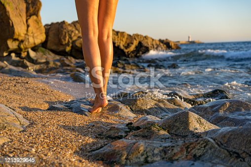 522909925 istock photo Woman with beautiful long legs walking along a rocky and sandy beach in Matosinhos, Portugal 1213929645