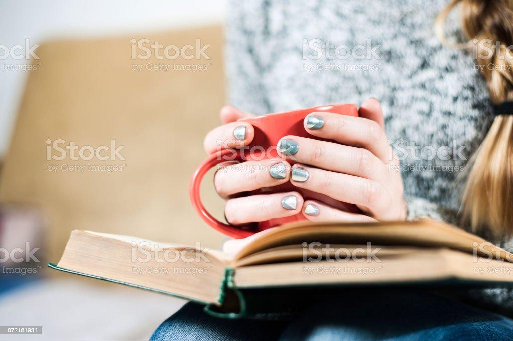 Frau mit schönen Maniküre hält eine Tasse Tee und ein Buch zu lesen – Foto