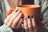 ココアのオレンジ色のカップを保持する美しいマニキュアを持つ女性