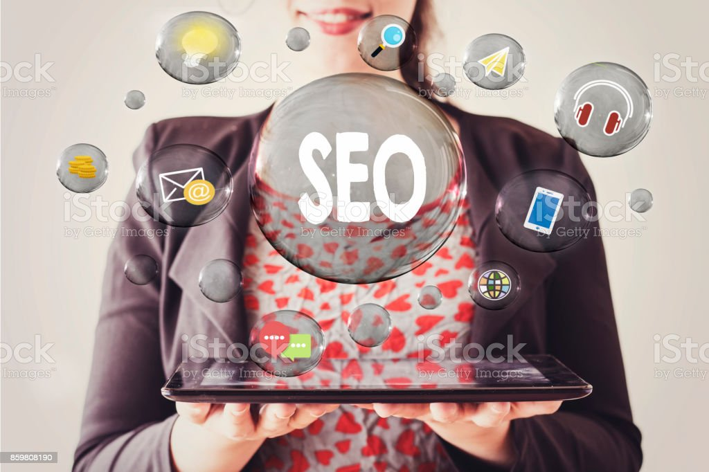 woman with beautiful smile holding a tablet and seo concept in transparent bubble stock photo