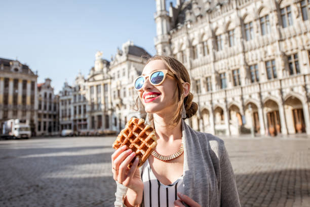 Woman with belgian waffle outdoors Young woman walking with waffle a traditional belgian pastry food in the center of Brussels city during the morning belgium stock pictures, royalty-free photos & images