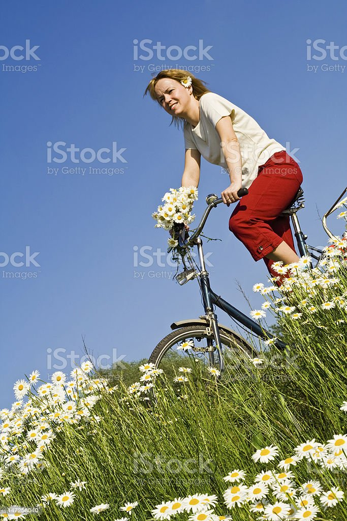Woman with bicycle among spring flowers royalty-free stock photo