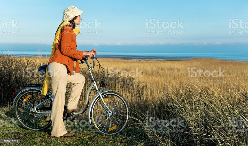 Woman with bicycle at coast of Sylt, Germany in winter stock photo