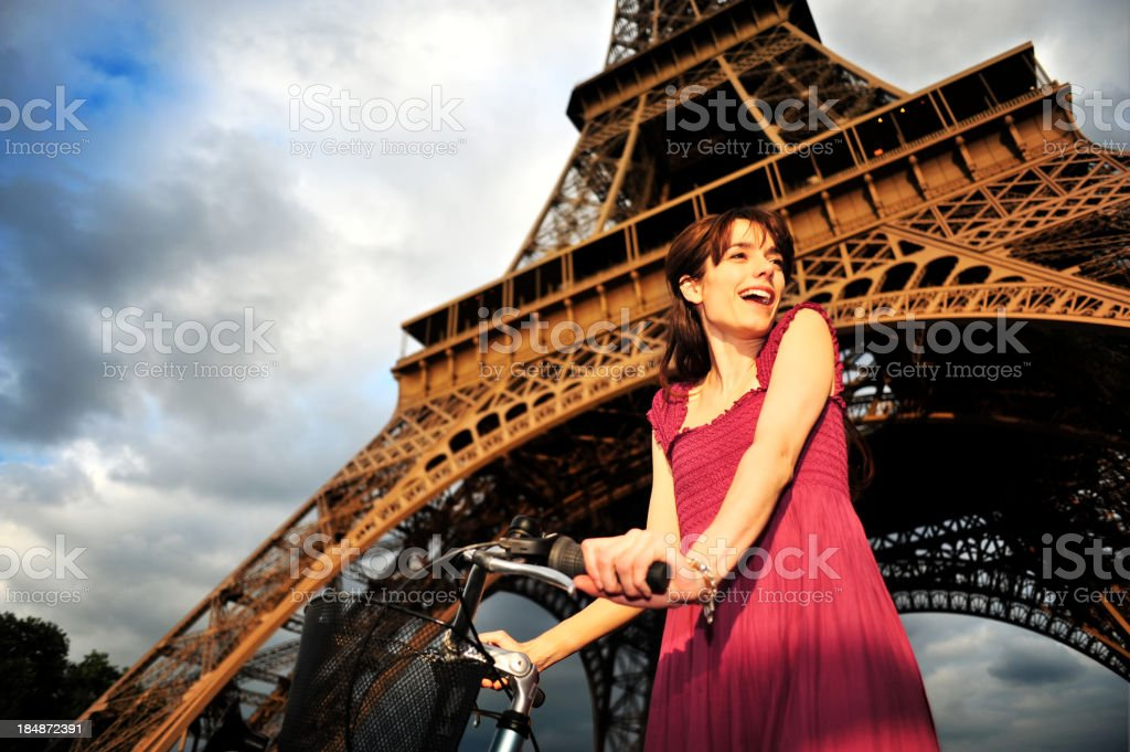 Woman with bicycle below Eiffel Tower in Paris royalty-free stock photo