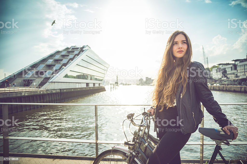 Woman with bicycle by the harbor stock photo