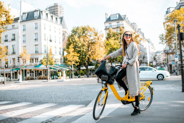 mujer con bicicleta en parís, francia - moda parisina fotografías e imágenes de stock