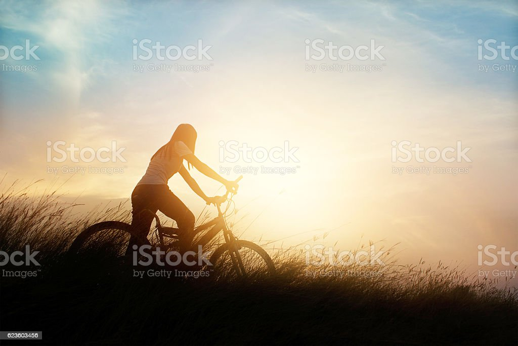 Woman with bicycle on rural road with grass, sunset background – Foto