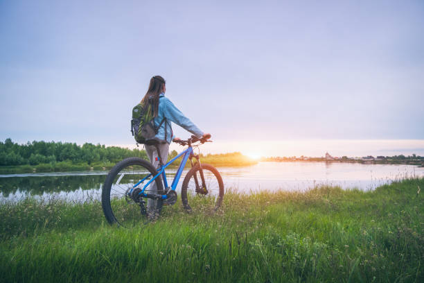 Woman with bicycle on the hill near the river at sunset in spring. Landscape with sporty girl with backpack riding a mountain bike, dirt road, green grass, water in summer. Sport and travel. Cycle stock photo