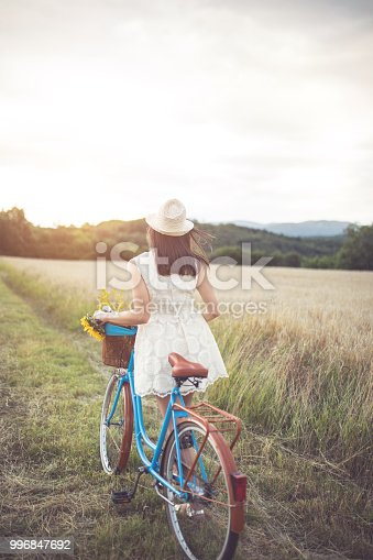 Woman with bicycle on wheat field.