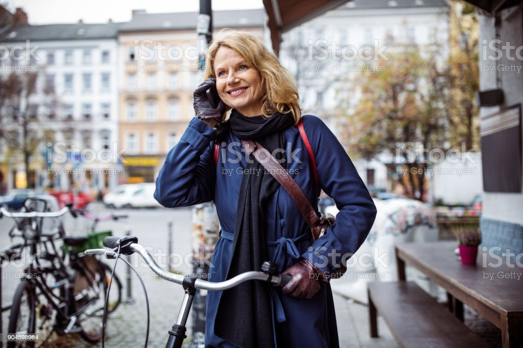 Woman with bicycle talking on mobile phone in city royalty-free stock photo