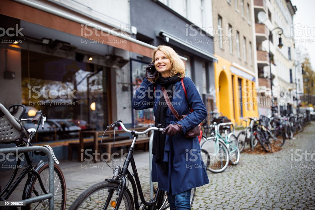 Woman with bicycle talking on phone in city royalty-free stock photo