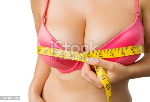 498310066istockphoto Woman with big boobs measuring her bust 512521013