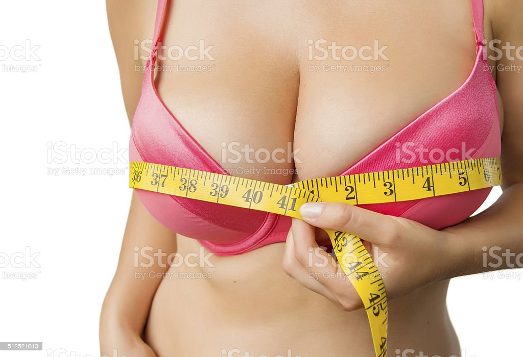 Woman with big boobs measuring her bust stock photo