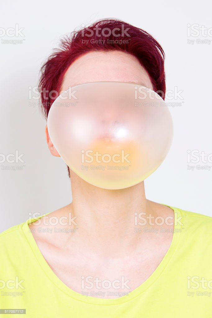 woman with big yellow bubble of chewing gum stock photo