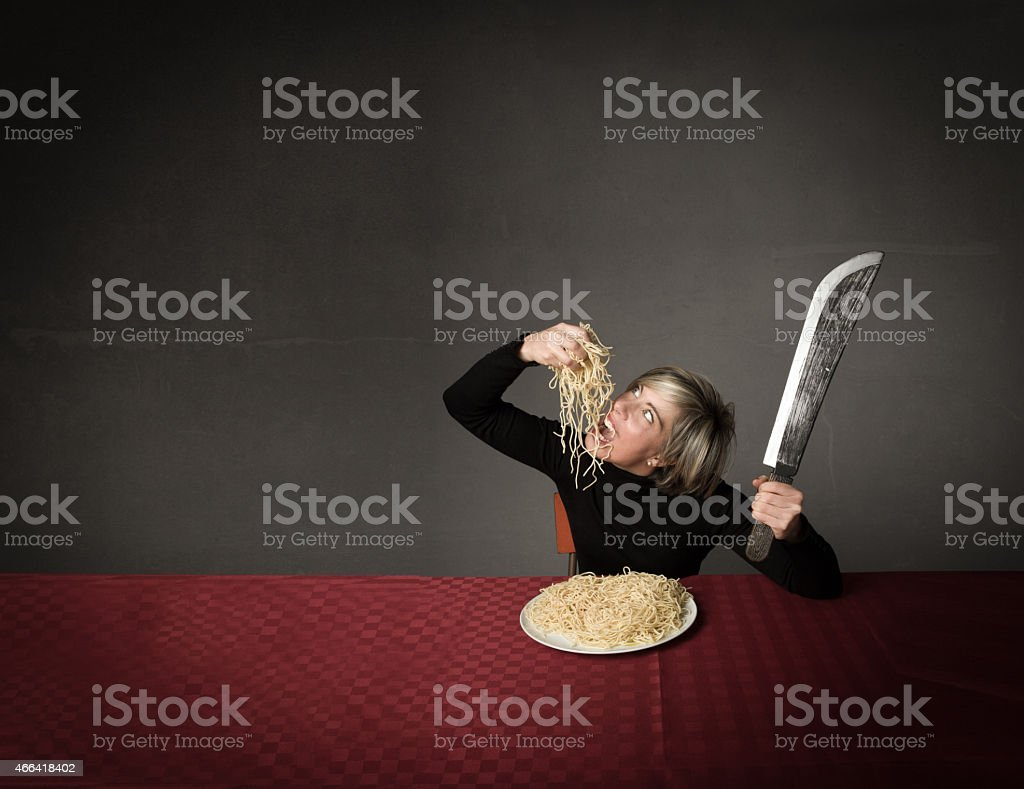 woman with bik knife eating italian spaghetti stock photo