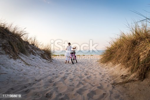 Woman with bike on beach at sunset