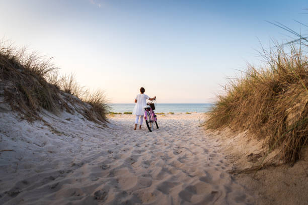 Frau mit Fahrrad am Strand bei Sonnenuntergang – Foto