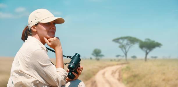 Woman with binoculars enjoying a beautiful view of the African savannah during a safari tour in Tanzania and Kenya stock photo