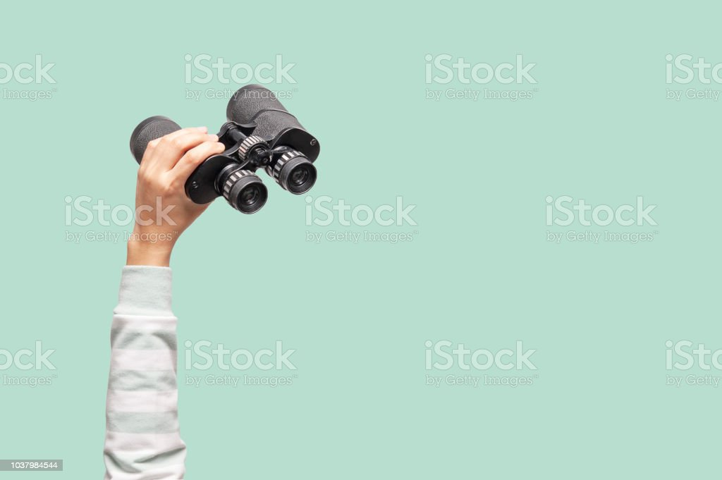 Woman with binoculars on green background stock photo