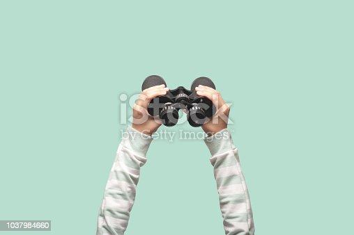 istock Woman with binoculars on green background 1037984660