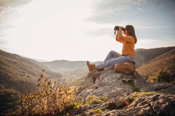 Woman with binoculars sitting on mountain peak in sunset stock photo