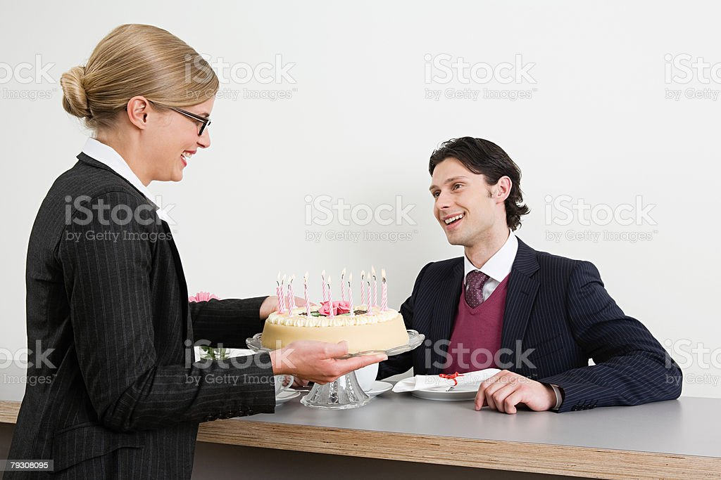 Woman with birthday cake for colleague 免版稅 stock photo