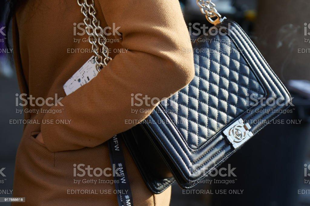 e803c0f868 Femme avec sac de cuir noir Chanel avec chaine en argent et un manteau  beige photo