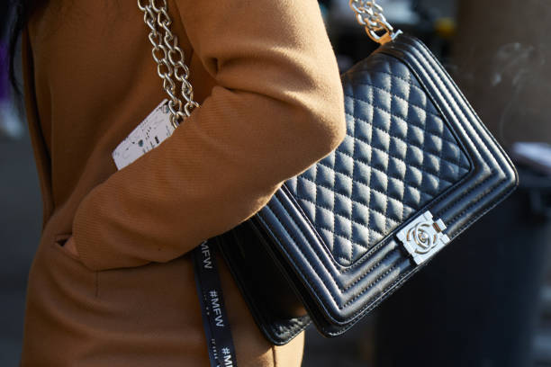 Woman with black Chanel leather bag with silver chain and beige coat MILAN - JANUARY 14: Woman with black Chanel leather bag with silver chain and beige coat before MSGM fashion show, Milan Fashion Week street style on January 14, 2018 in Milan. brand name stock pictures, royalty-free photos & images