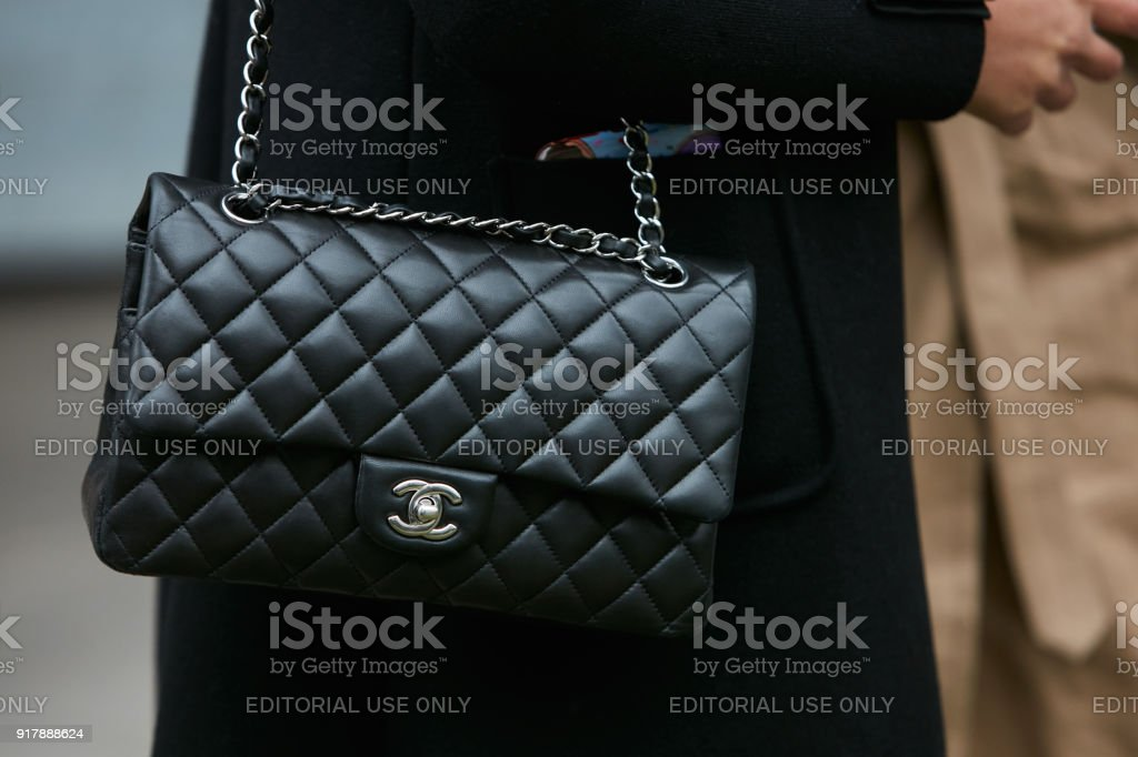 Woman with black Chanel leather bag with silver chain