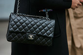 シルバー チェーン付き黒のシャネルの革バッグを持つ女性