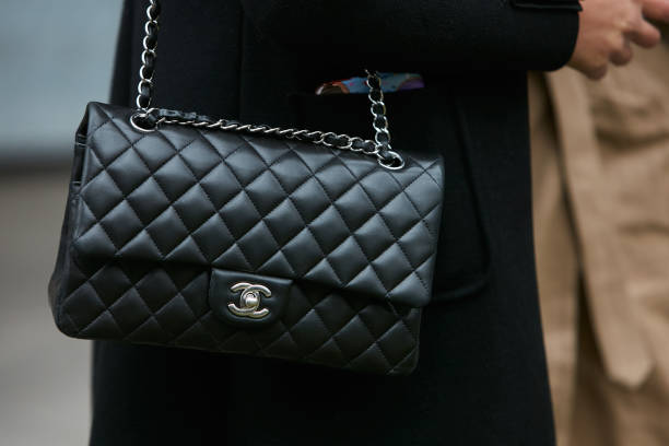Woman with black Chanel leather bag with silver chain MILAN - JANUARY 15: Woman with black Chanel leather bag with silver chain before Giorgio Armani fashion show, Milan Fashion Week street style on January 15, 2018 in Milan. bag stock pictures, royalty-free photos & images
