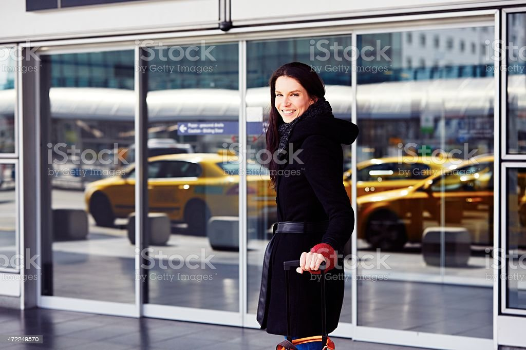 Woman with black coat at the entryway of an airport stock photo