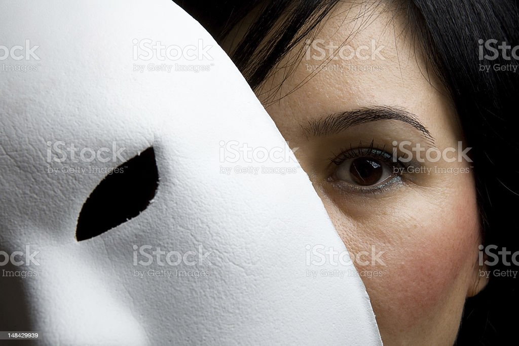 Woman With Black Hair And Eyes Peeking Behind White Mask royalty-free stock photo