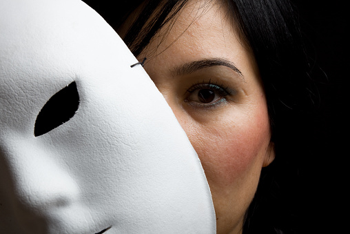 A young woman with black hair and black eyes looking at the camera from behind a white mask.The photo was shot with a full from DSLR camera in horizontal close up composition.The mask is on the left side of frame.