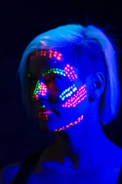 Woman with black light paint on face, profile, head and shoulders. stock photo
