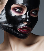 Woman with black peel-off mask