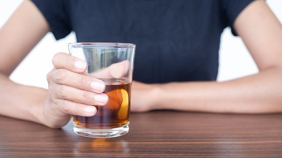 Woman with black t-shirt holding Whiskey or alcohol in glass on wooden table.