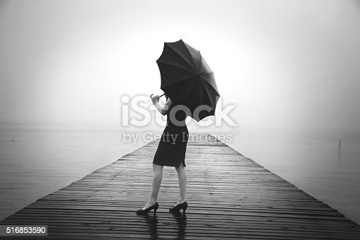 istock woman with black umbrella looking infinity in a surreal place 516853590