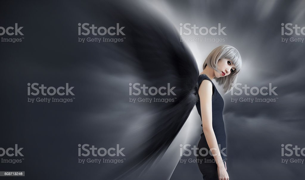 Woman with black wing and silver hair on dark background stock photo