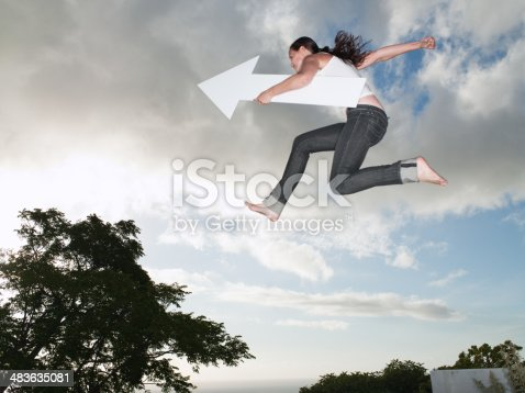 istock Woman with blank arrow leaping outdoors 483635081