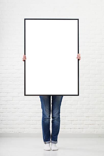 frau mit leeren poster an wand-hintergrund - unterrichtsplanung vorlagen stock-fotos und bilder