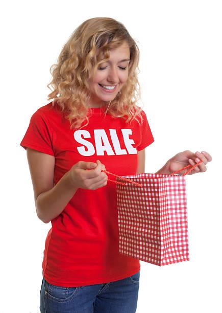 frau mit blonden haaren und shopping-tasche in sales-hemd - engelsflügel kaufen stock-fotos und bilder