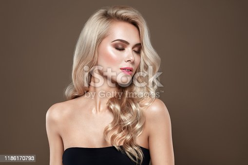 Woman with blonde hair Portrait with closed eyes and Healthy Long Shiny Wavy hair style. Volume shampoo. Blond Curly permed Hair and bright makeup.  Beauty salon and haircare concept.