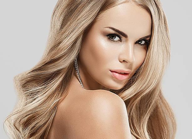 woman with blonde hair. studio shot. gray background. - frisuren für schulterlanges haar stock-fotos und bilder