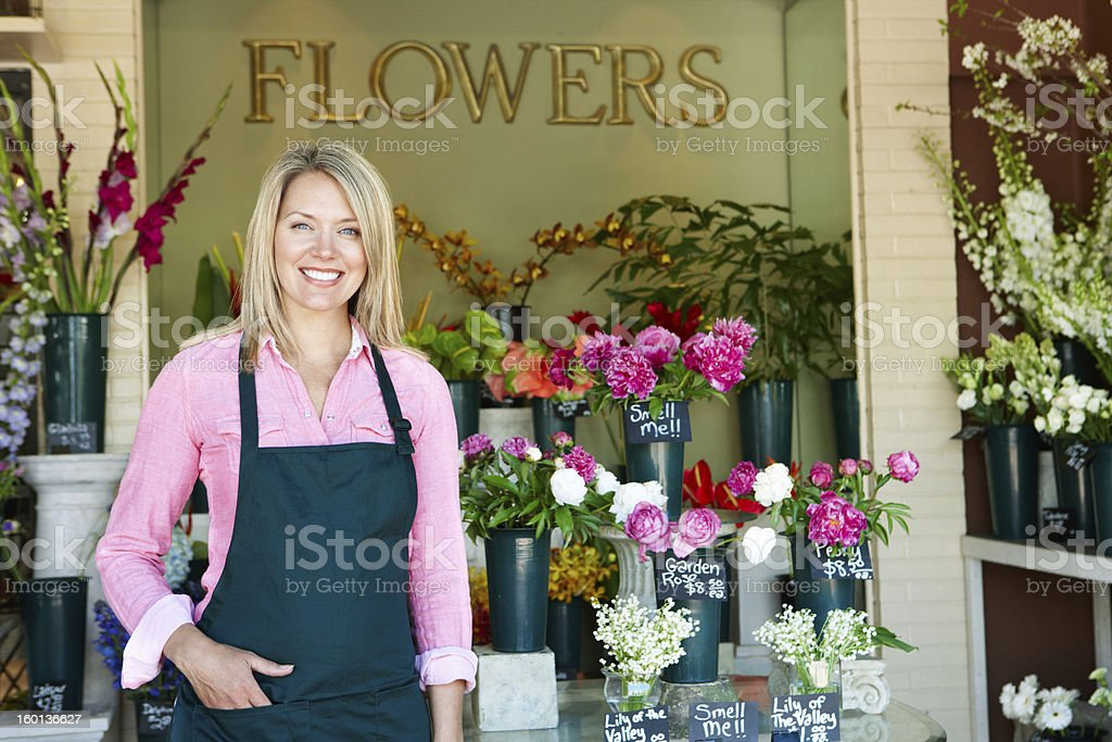 Woman with blue apron standing by flowers at a flower shop stock photo