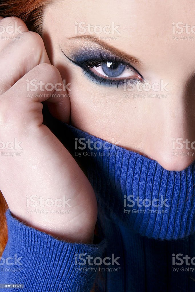 Woman with Blue Eyes Holding Turtleneck Up to Mouth stock photo