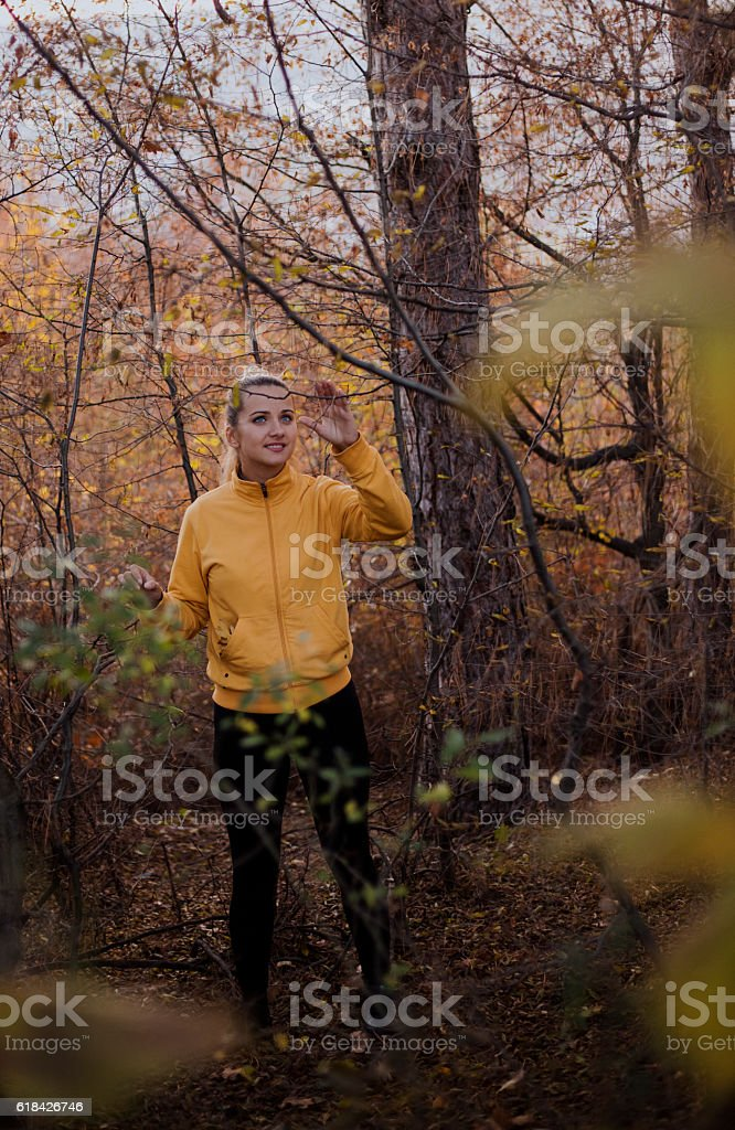 Woman with blue eyes in autumn forest at sunset. stock photo